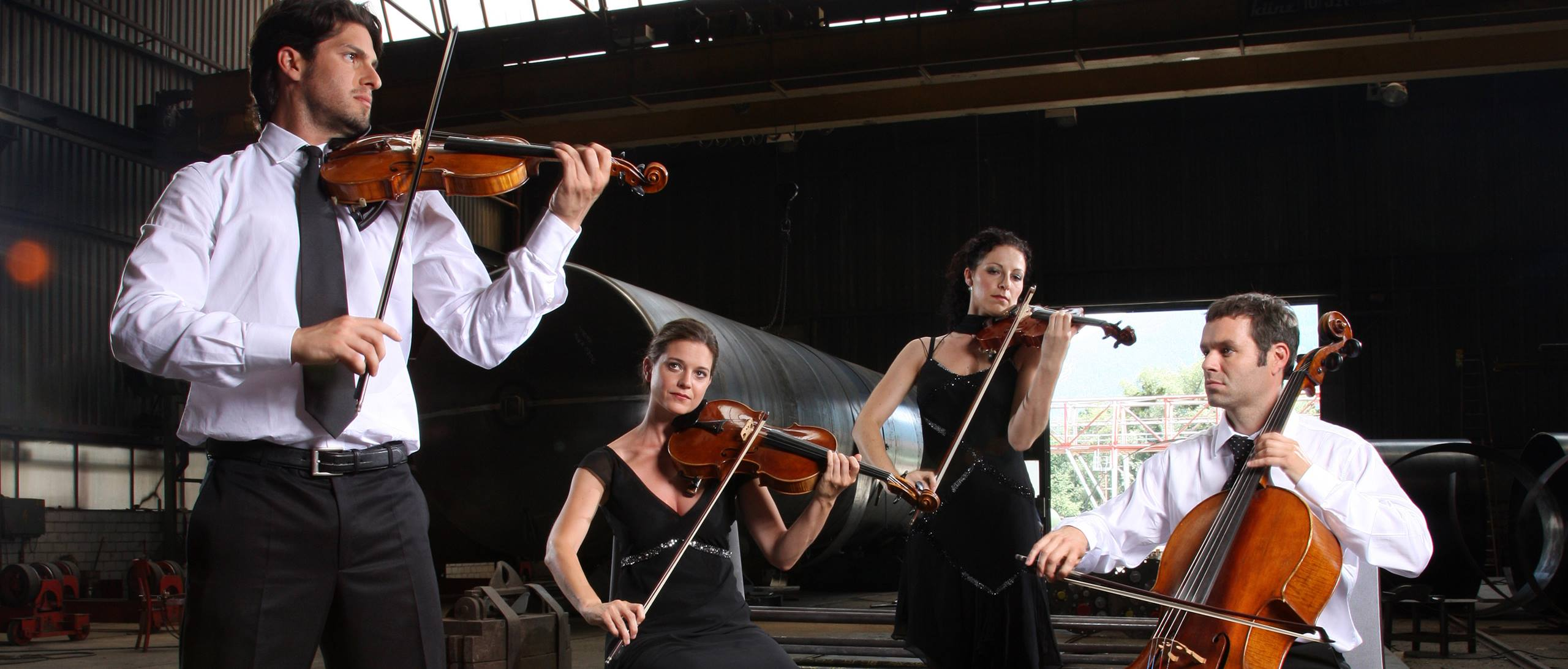 Four people playing violin and cello