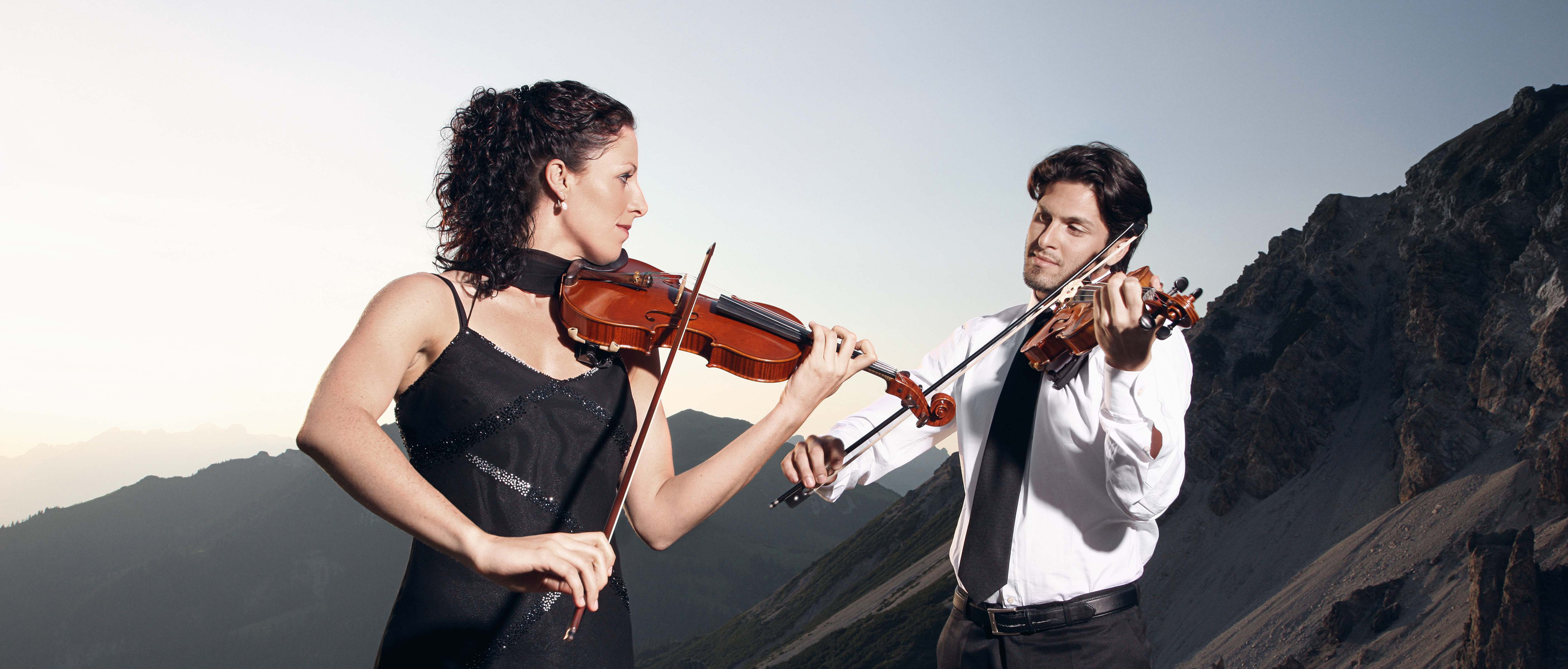 Two people are playing violin