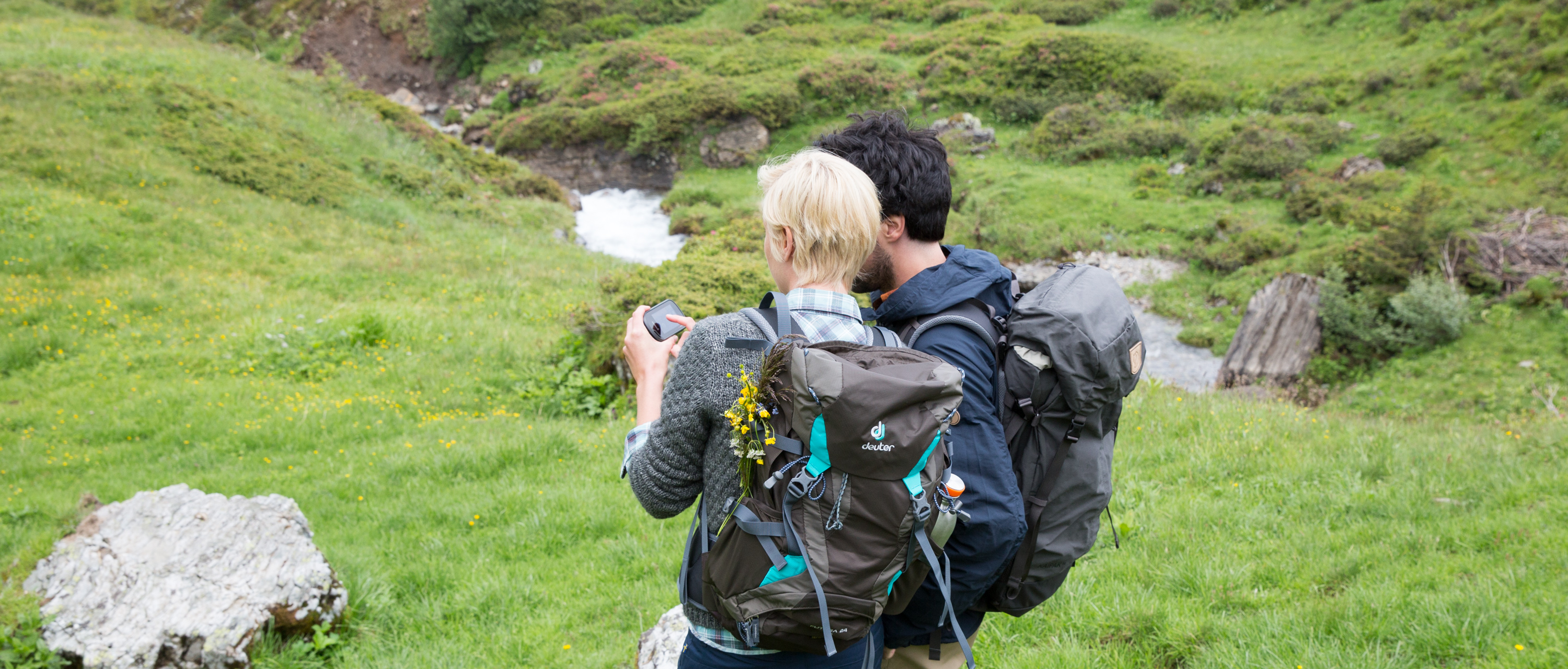 Two people are looking at photos while hiking