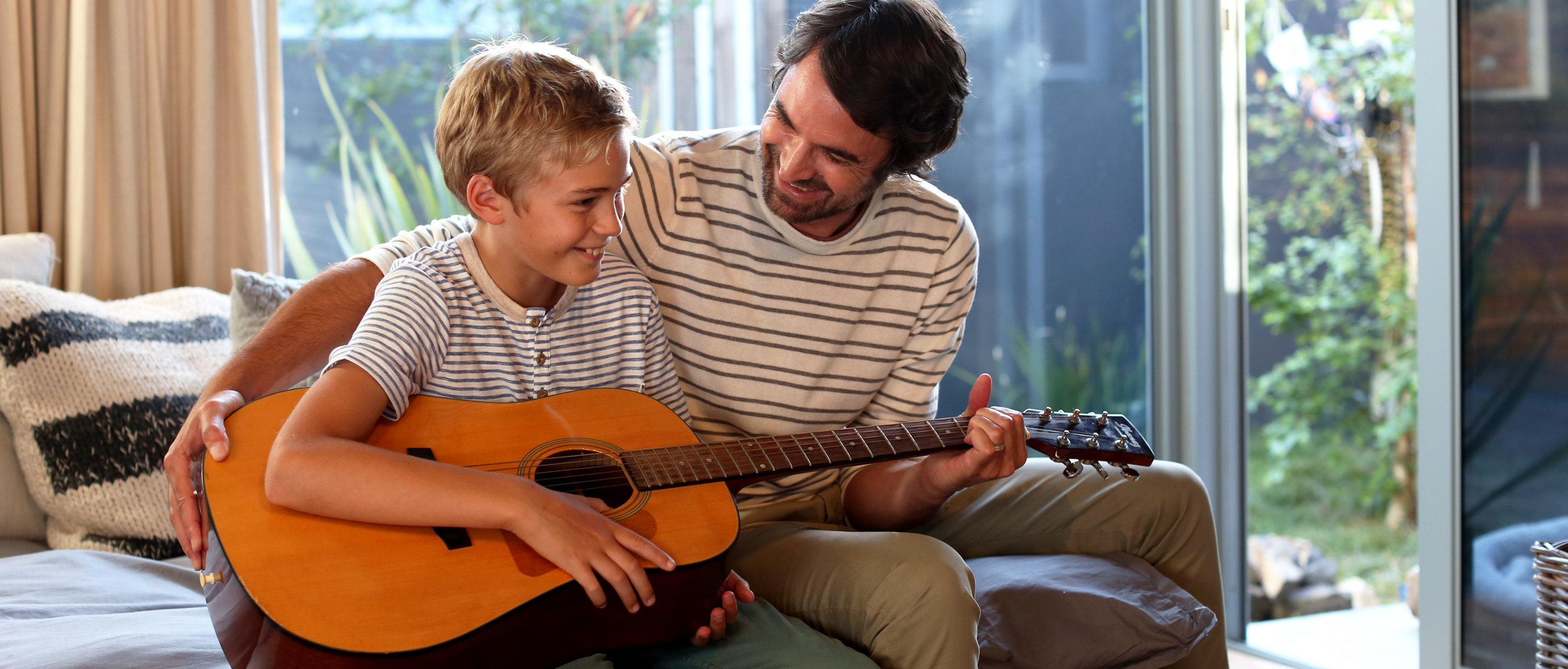 Father plays the guitar with his son